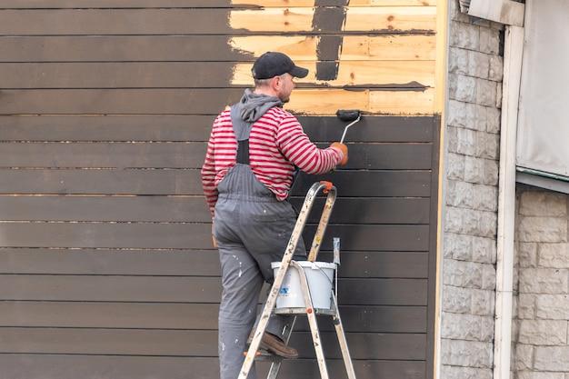 Een man die houten muur buiten schildert