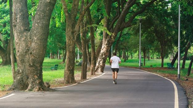 Een man die in het park loopt.