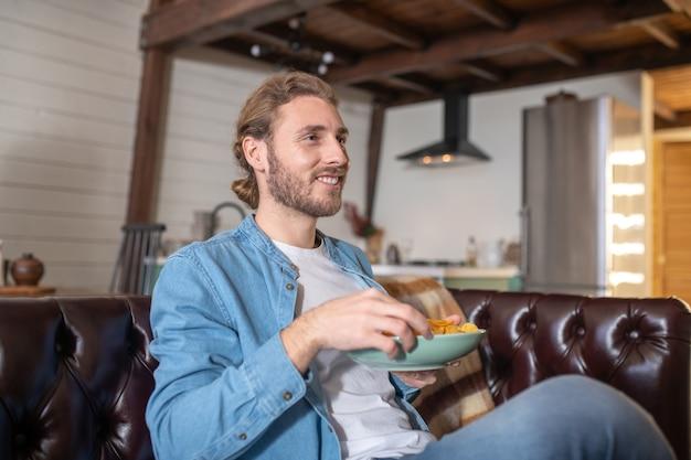 Een man die junkfood eet terwijl hij thuis blijft