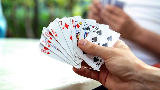 Een man die kaarten speelt met andere mensen die een kaartspel vasthouden