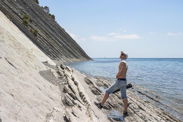Een man die langs het wilde stenen strand liep, stopte en kijkt omhoog. de badplaats gelendzhik. rusland, kust van de zwarte zee
