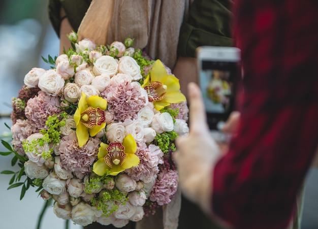 Een man die met telefoon een prachtig wit en paars bruidsboeket fotografeert
