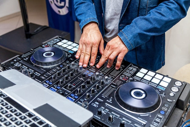 Een man die muziek speelt op een audiomixer en tracks mixt op het strandfeest