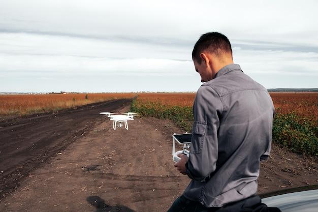 Een man die naast de auto staat, lanceert een drone. drone vlucht in geel veld