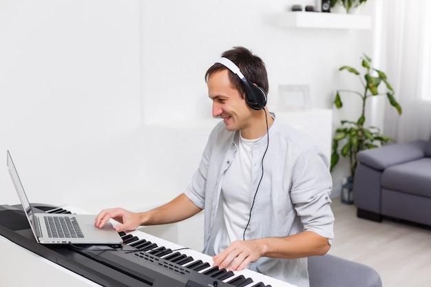 Een man die online piano leert spelen met een computer die thuis blijft. begrippen van autodidact, thuis blijven en online werken