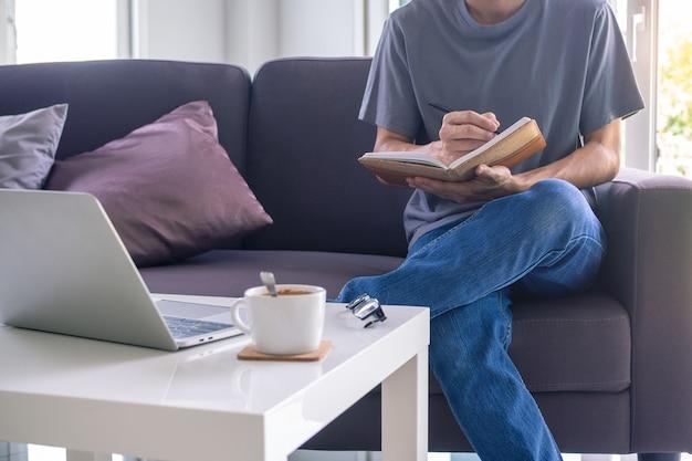 Een man die online werkt of studeert in de woonkamer op de bank.