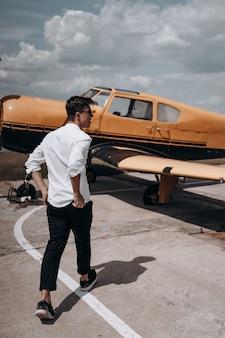 Een man die op de achtergrond van een klein motorvliegtuig staat.