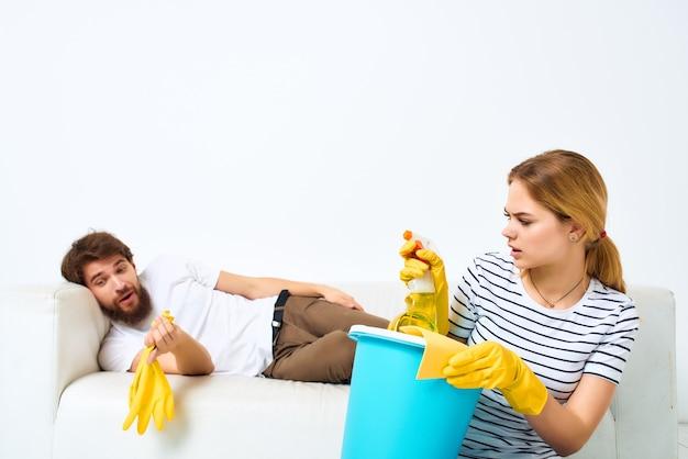 Een man die op de bank ligt, huisvrouw die het huis schoonmaakt