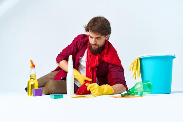 Een man die op de vloer zit en de professionele levensstijl van het appartement schoonmaakt