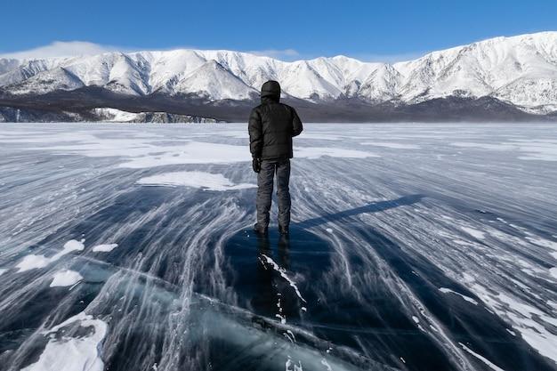 Een man die op een glad oppervlak van een bevroren bergmeer staat tijdens een sterke wind in de winter.