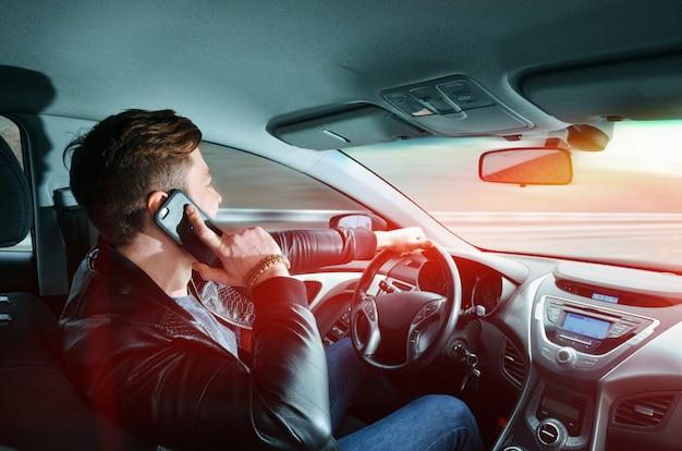 Een man die op een mobiele telefoon in een auto praat