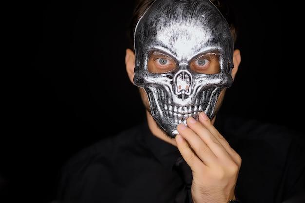 Een man die op een zwarte achtergrond staat, draagt een skeletmasker