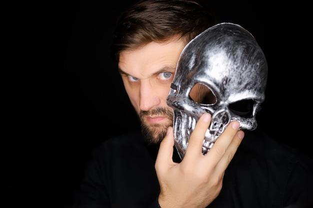 Een man die op een zwarte achtergrond staat kijkt uit onder een skeletmasker dat hij op zijn gezicht wil zetten