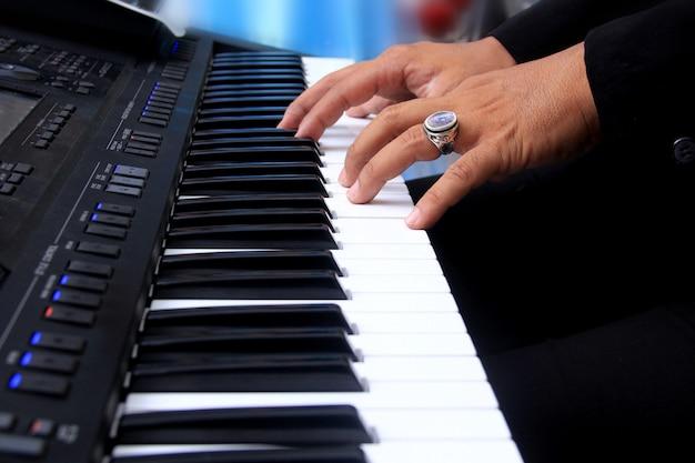 Een man die piano klaviertoetsen speelt