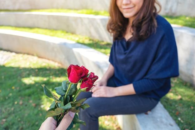 Een man die rood roze bloemen geeft aan mooie vriendin op valentijnsdag in de buitenlucht
