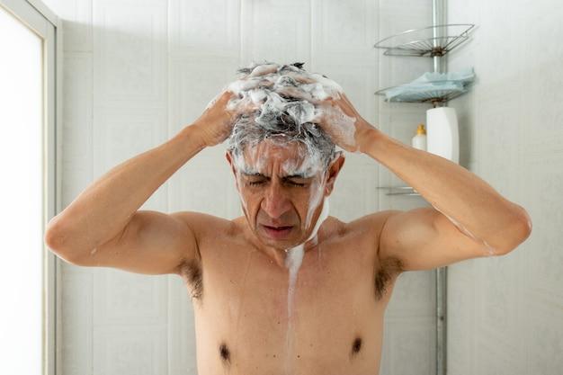 Een man die 's ochtends onder de douche staat