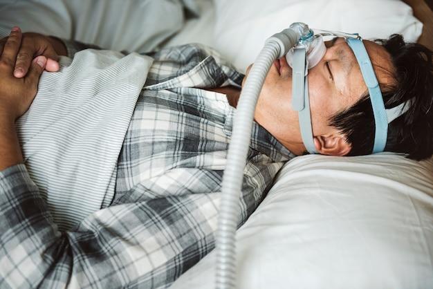 Een man die slaapt met een anti-snurkende kinband