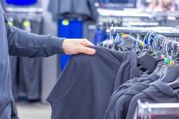Een man die sweatshirt of hoodie kiest in een sportwinkel