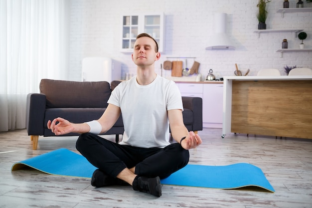 Een man die thuis yoga-oefeningen doet, zittend op de vloer van de woonkamer. gezonde levensstijl.