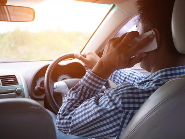 Een man die tijdens het rijden een mobiele telefoon gebruikt, kan ongelukken veroorzaken