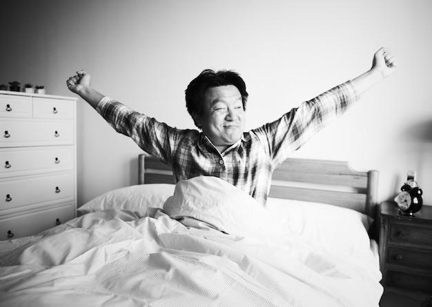 Een man die wakker wordt op het bed