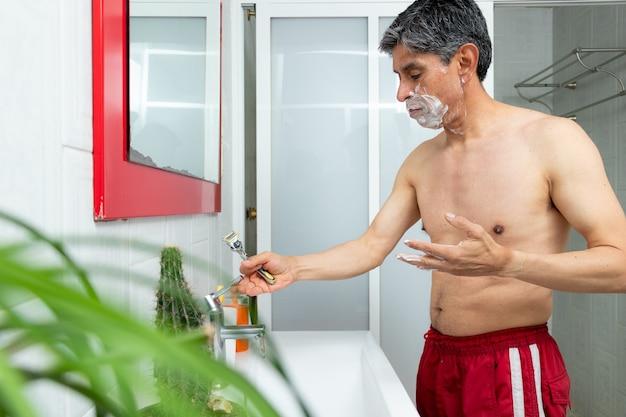Een man die zijn gezicht scheert in de badkamer