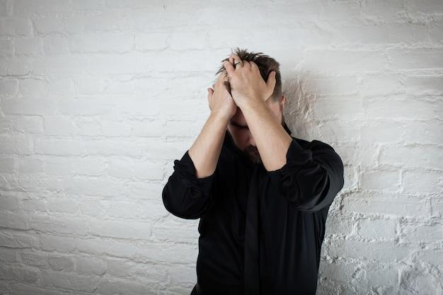 Een man die zijn hoofd vasthoudt. het concept van depressie.