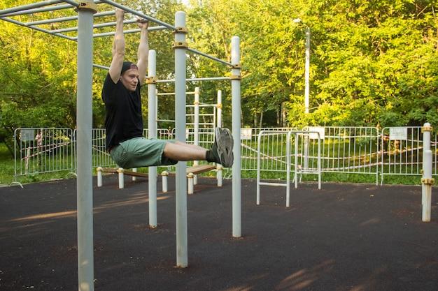 Een man doet een oefening op een rekstok in het park. het concept van sport, fitness en een gezonde levensstijl is een man die een oefening uitvoert op een rekstok op een sportveld in een stadspark.
