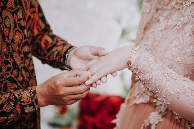Een man doet een ring om de vinger van een vrouw