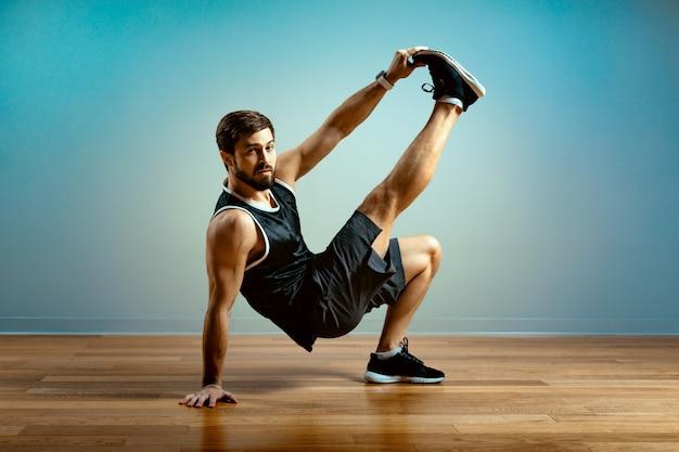 Een man doet functionele oefeningen in de sportschool op een grijze achtergrond.