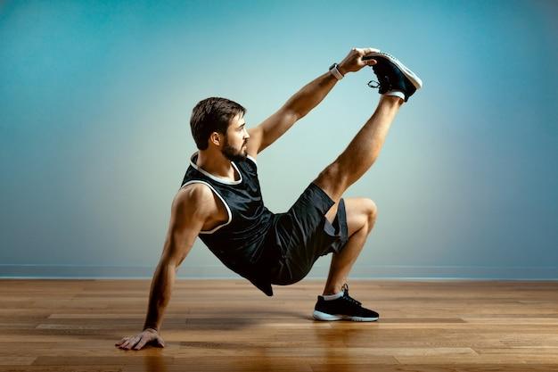 Een man doet functionele oefeningen in de sportschool op een grijze achtergrond