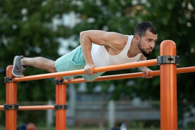 Een man doet overdag push-ups op de tralies op straat