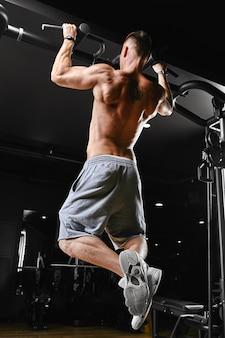 Een man doet pull-ups op de rekstokgym, een donkere achtergrond, een mooi lichaam, fitnessmotivatie.