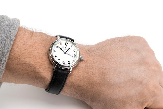 Een man draagt een horloge met een zwarte leren band op een witte achtergrond.