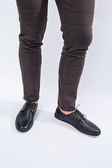 Een man draagt klassieke zwarte schoenen gemaakt van natuurlijk leer aan kant, schoenen voor mannen in zakelijke stijl. hoge kwaliteit foto