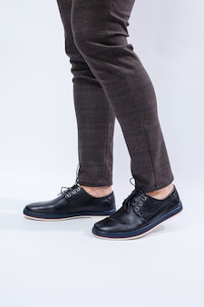 Een man draagt klassieke zwarte schoenen gemaakt van natuurlijk leer aan kant, schoenen voor mannen in zakelijke stijl