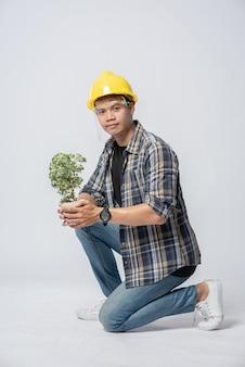 Een man draagt oranje handschoenen en gaat zitten om een plantenpot in huis te houden.