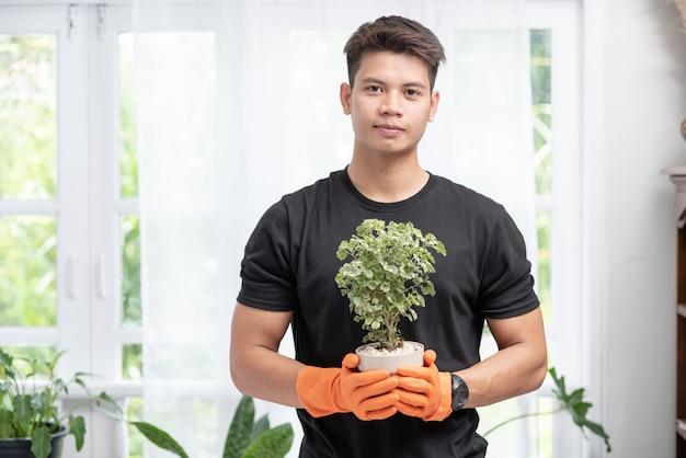 Een man draagt oranje handschoenen en staat op om een plantenpot in huis te houden.