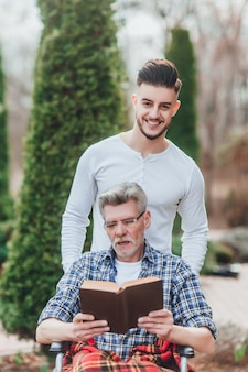 Een man draagt zijn vader, ze hebben plezier en ze lachen terwijl ze een boek lezen