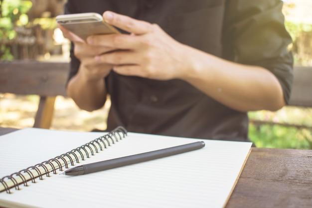 Een man draagt zwarte shirts. met zijn telefoon en open boek met een pen op een houten tafel.