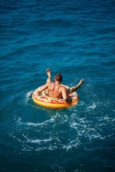 Een man drijft op een opblaasbare ring in de zee met blauw water. vakantie aan zee op een zonnige dag. turkije vakantie concept