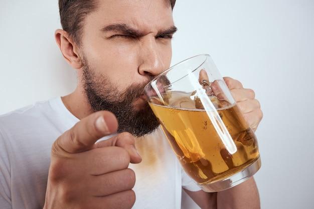 Een man drinkt bier uit een glas, alcoholisme
