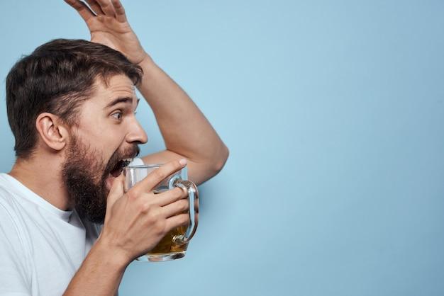 Een man drinkt bier uit een glas en eet junk fried fast food