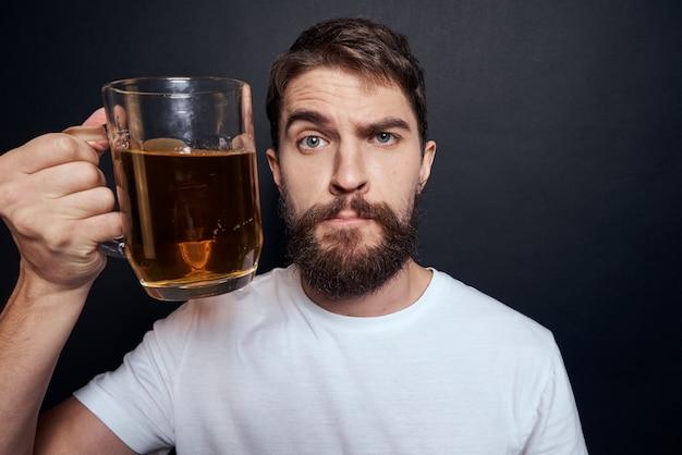 Een man drinkt bier uit een glas en eet junk gefrituurd fastfood