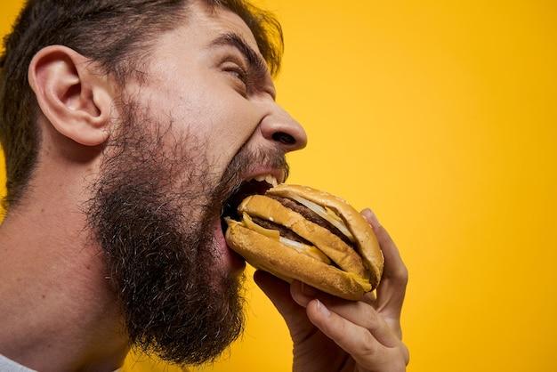 Een man drinkt bier uit een glas en eet junkfried fastfood