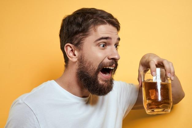 Een man drinkt bier uit een glas