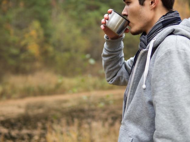 Een man drinkt hete thee uit een thermosfles in de natuur in de herfst