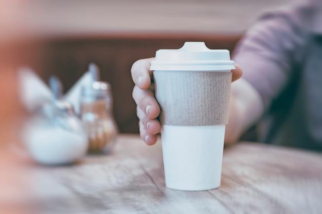 Een man drinkt koffie in een restaurant aan een houten tafel. mockup van een kartonnen eco-mok.