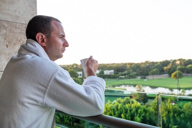 Een man drinkt op vakantie thee op het balkon van een hotel. zomer concept