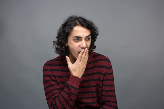 Een man dut terwijl hij zijn mond sluit met de palm